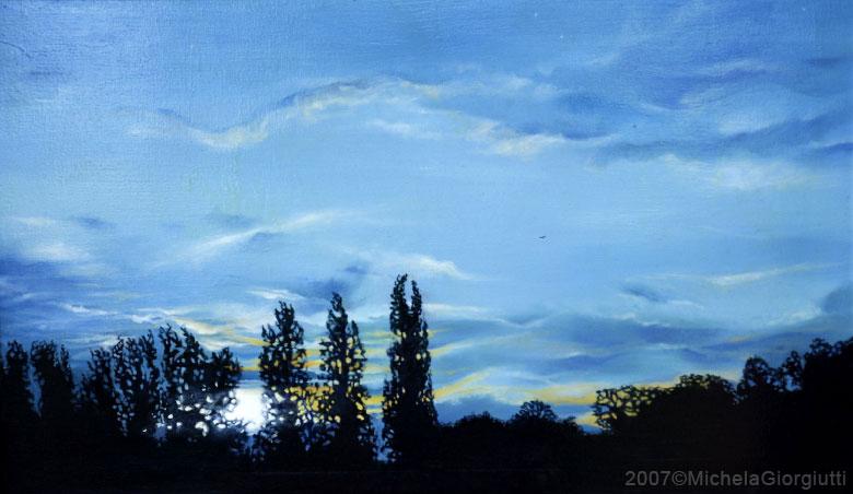 Cielo blu al tramonto con riflessi gialli e silhouette di alberi